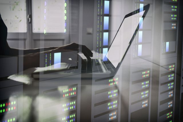 Woman's hands working on laptop in data center double exposure